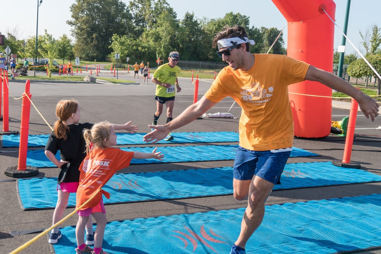 Participant giving a child a high-5 at the finish line