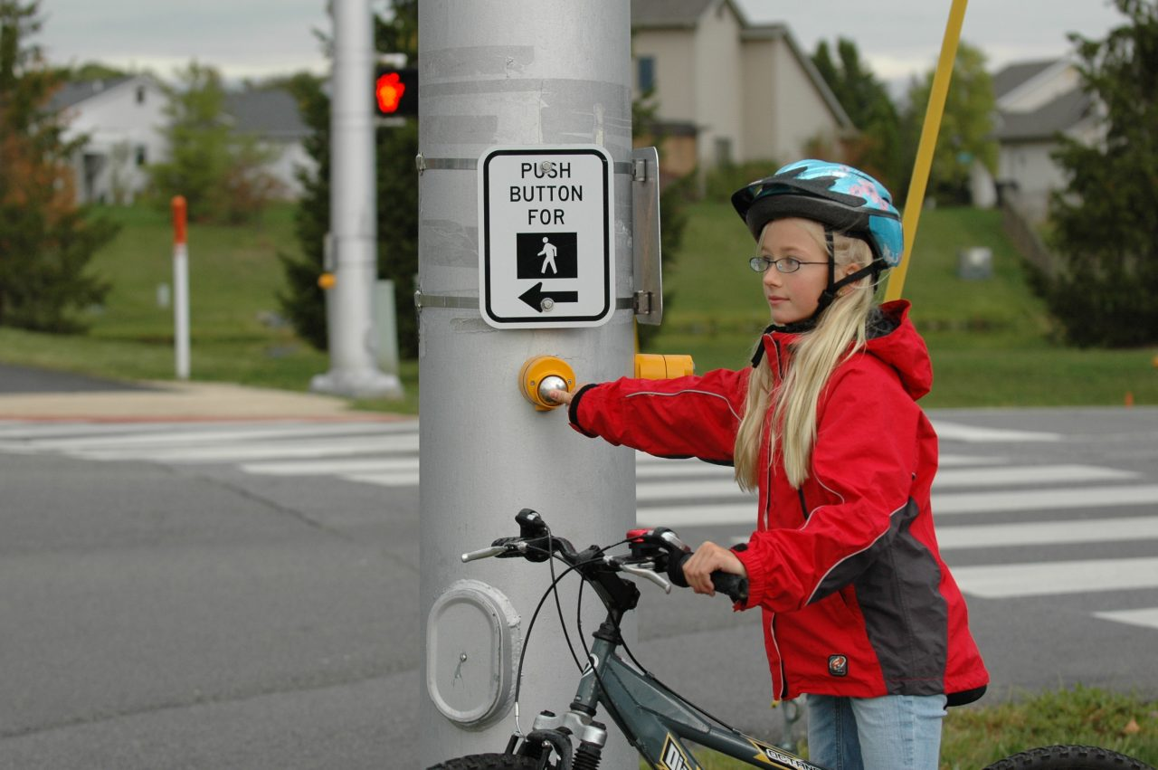 Child using cross-walk button for signal.